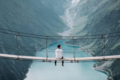 Über einer weiten Schlucht, auf einer Hängebrücke sitzt ein junger Mann