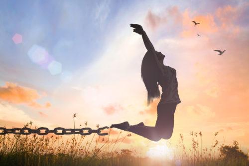 Frau springt über die Wiese von Ketten befreit